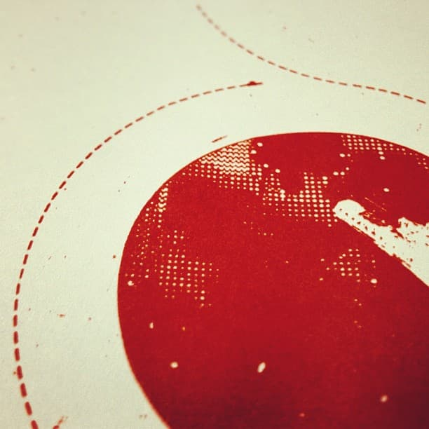 Closeup of a screen print depicting a spaceship orbiting a red planet